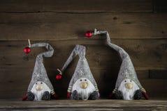 Trois lutins faits main sur le fond en bois utilisant le chapeau de Santa pour c Images stock