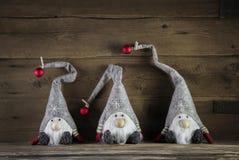 Trois lutins faits main sur le fond en bois utilisant le chapeau de Santa pour c Image stock