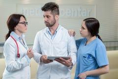Trois médecins à l'aide d'un comprimé dans un bureau lumineux Photos libres de droits