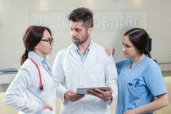 Trois médecins à l'aide d'un comprimé dans un bureau lumineux Images libres de droits