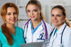 Trois médecins féminins de sourire de médecine dans le bureau regardant dans le camer Photos stock