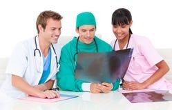 Trois médecins gais regardant un rayon de x images stock