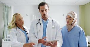 Trois médecins utilisant la tablette dans la salle d'hôpital 4k banque de vidéos