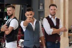 Trois maîtres posant avec des ciseaux dans le raseur-coiffeur images stock