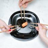 Trois mains avec des baguettes et des sushi Fond en bois blanc Images stock