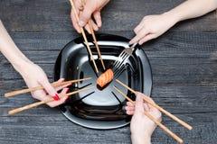 Trois mains avec des baguettes, une avec la fourchette et sushi Bois noir Photos stock
