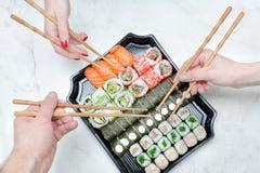 Trois mains avec l'ensemble de baguettes et de sushi Vue supérieure Photo stock