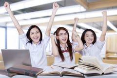 Trois mains heureuses d'augmenter d'étudiants dans la classe Photos stock