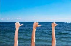 Trois mains indiquent la direction de la mer Image stock