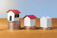 Trois maison de papier sur des piles du ` s de pièce de monnaie, hypothèque, prêts et Co de s'enregistrer Photos stock
