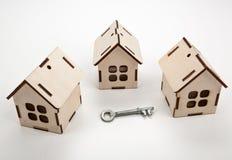 Trois maisons miniatures en bois et une clé de porte sur un backgrou blanc photographie stock libre de droits