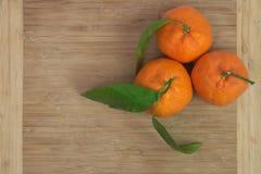 Trois mandarines avec des feuilles sur le conseil en bois Photo stock