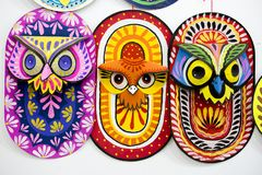 Trois masques colorés de hibou accrochant sur le mur d'institut d'art Photo stock