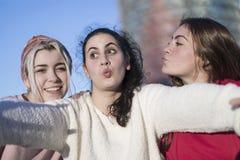 Trois meilleures amies heureuses faisant dehors le selfie sur le smartphon Photo stock