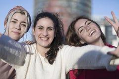 Trois meilleures amies heureuses faisant dehors le selfie sur le smartphon Photos stock