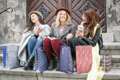 Trois meilleurs amis appréciant après l'achat Se reposer de jeunes filles Photo stock