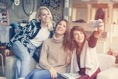 Trois meilleurs amis dans un café Jeunes femmes faisant l'auto-photo Photographie stock