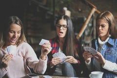 Trois meilleurs amis en café jouant ensemble des cartes de jeu Photo libre de droits