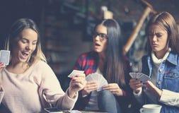 Trois meilleurs amis en café jouant ensemble des cartes de jeu Cl Image libre de droits