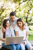 Trois meilleurs amis en parc appréciant et dactylographiant sur l'ordinateur portable Image libre de droits