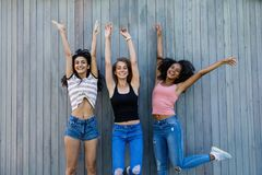 Trois meilleurs amis féminins sautant ensemble Images stock