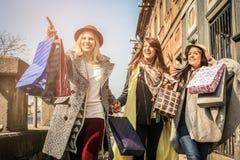 Trois meilleurs amis marchant sur la rue Jeune fille montrant a Photographie stock