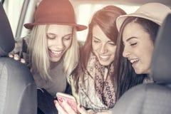 Trois meilleurs amis montant dans la voiture Photos stock