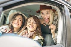 Trois meilleurs amis montant dans la voiture Photos libres de droits