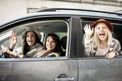 Trois meilleurs amis montant dans la voiture Photographie stock libre de droits