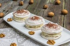 Trois meringues de noix avec du cacao avec des noix à l'arrière-plan photo stock