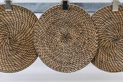 Trois modèles tissés par osier brun accrochant contre le mur blanc images stock