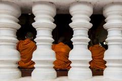 Trois moines dans des robes longues oranges derrière quatre piliers image libre de droits