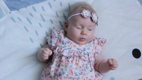 Trois mois de bébé avec des yeux bleus Enfant nouveau-né, petite fille paisible et attentive adorable semblant le sourire étonné  clips vidéos