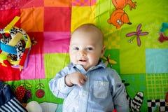 Trois mois heureux de bébé garçon, jouant à la maison sur un a coloré Images libres de droits
