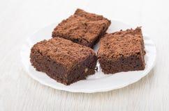 Trois morceaux de gâteau de chocolat dans le plat blanc sur la table Photo libre de droits