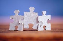 Trois morceaux de puzzle denteux sur une table Images stock