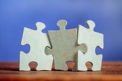 Trois morceaux de puzzle denteux sur une table Photos libres de droits