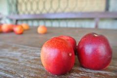 Trois nectarines rouges mûres sur la table en bois rustique Photographie stock libre de droits
