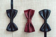 Trois noeuds papillon, deux noirs et un rouge Team le travail, carrière, hippie, épousant le concept photographie stock libre de droits