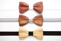 Trois noeuds papillon en bois avec les rubans blancs, gris et noirs Configuration plate, d'isolement Team le travail, carrière, m Photos stock