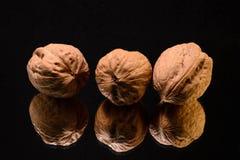 Trois noix reflétées Photos stock