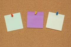 Trois notes collantes colorées avec les punaises et l'espace vide, d'isolement sur le fond de liège, concept d'école photo stock