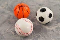 Trois nouvelles boules en caoutchouc molles du football et de basket-ball et de base-ball sous la forme de triangle image stock
