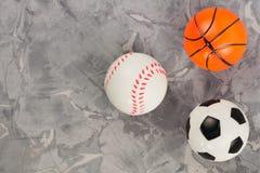 Trois nouvelles boules en caoutchouc molles du football et de basket-ball et de base-ball sous la forme de triangle sur le vieux  image stock