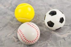Trois nouvelles boules en caoutchouc molles du football et de tennis et de base-ball sous la forme de triangle images stock