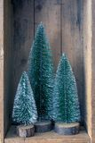Trois objets d'arbre de Noël dans une boîte en bois photos stock