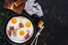 Trois oeufs au plat avec le lard dans une poêle avec du pain grillé, fond rustique foncé Vue supérieure, l'espace pour le texte photographie stock libre de droits