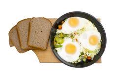 Trois oeufs avec des vegatables sur la poêle d'isolement sur le fond blanc photos libres de droits