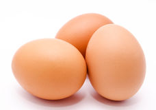 Trois oeufs bruns de poulet d'isolement sur un fond blanc Image libre de droits