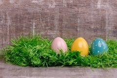 Trois oeufs colorés sur une herbe verte devant un fond en bois Carte de voeux de Pâques Image stock